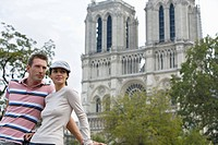 Young couple enjoying view in front of Notre Dame Cathedral, Paris, France