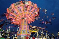 Illuminated fairground rides at night, Oktoberfest, Munich, Germany