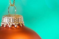 Orange Christmas bauble with green background, close_up