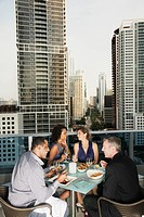 Couples eating dinner on urban balcony
