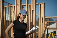 Hispanic woman holding blueprints at construction site