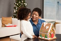 Grandmother and granddaughter looking at gingerbread house