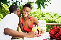 African couple drinking orange juice on patio