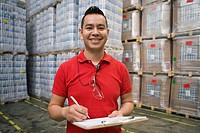 Hispanic man with clipboard smiling in warehouse