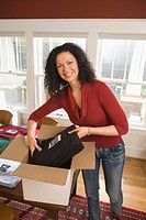 Mixed race woman packaging t_shirts in home office