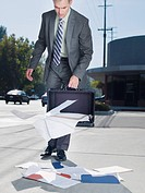 Businessman dropping papers from briefcase