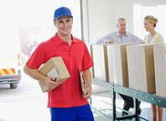 Delivery man holding cardboard box in warehouse (thumbnail)