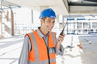 Worker talking on walkie_talkie on construction site
