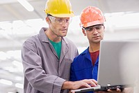 Workers in coveralls, hard_hats and safety goggles using laptop