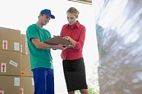 Businesswoman reviewing paperwork with delivery man