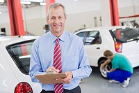Businessman holding clipboard in auto repair shop