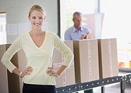 Businesswoman standing near conveyor belt in warehouse