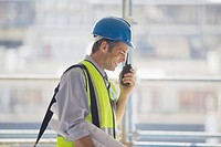 Businessman in hard_hat and safety vest talking on walkie_talkie
