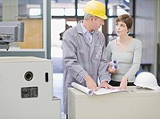 Businesswoman reviewing blueprints with construction worker