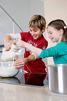 brother and sister mixing dough in bowl together