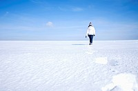rear view of young woman walking through snow