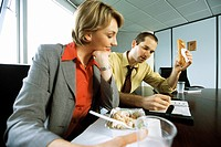 Business associates discussing calendar event over casual lunch in conference room