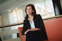 Businesswoman sitting with cell phone in hand, portrait