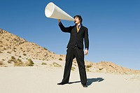 Businessman Using Megaphone in Desert