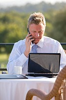 Businessman using cell phone and laptop on cafe patio