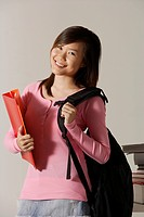 Young woman carrying back pack and folder