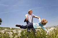 father swinging son in meadow