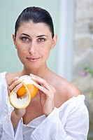 A female beauty peeling an orange