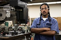Serious Hispanic man with arms crossed in machine shop