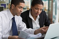 Businessman and businesswoman reviewing paperwork