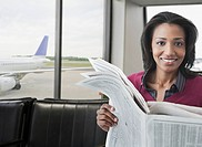 Smiling African woman reading newspaper in airport lounge