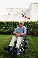 Smiling Hispanic man sitting in wheelchair on lawn