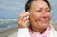 A senior woman with a seashell to her ear
