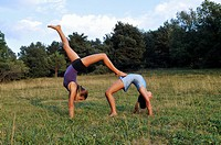 two young gymnasts doing gymnastics in a meadow in the Pyrenees