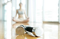 Two dumbbells placed closed to each other with a woman performing yoga is seen at the background