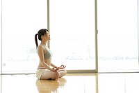 A young woman in deep meditation while doing yoga in the gym