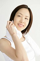 A young woman smiles as she wipes her face with a towel after an exercise