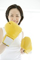 A young woman smiles with the gloves on as she poses against the camera (thumbnail)