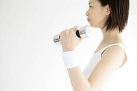Side view of a young woman lifting the dumbbell (thumbnail)