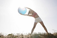 A young woman holds a huge ball as she bends from her abs while exercising under the sunlight