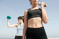 Two women hold dumbbells under the sky