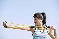 A woman working out as she stretches a rope tightly with her hands