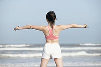 Rear view of a woman stretching her arms at the seashore with dumbbells in her hands