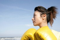 A side view of a woman wearing boxing gloves seen near the sea