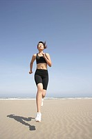 A young woman jogs along the beach on a bright sunny day