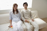 A young couple sitting on a sofa (thumbnail)