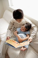 A young father reading a book to his daughter