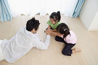 A young father playing with two girls