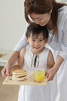 A girl holding a tray with some pancakes