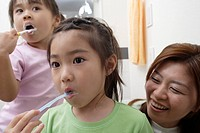 Two girls brushing teeth as mother watches them