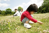 A small boy stares at the grass in the garden as his parents looks on (thumbnail)
